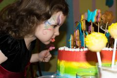 Child bite a rainbow cake royalty free stock images