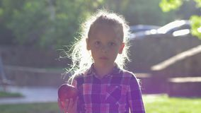 Child bites apple in backlight, little girl dressed shirt chews juicy ripe fruit and look on camera at nature. Child bites apple in backlight, little girl stock video footage