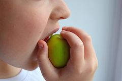 A child bites a green apple. Healthy lifestyle. royalty free stock photo
