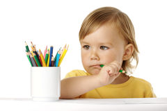 Child bites green crayon and thinks about ideas Stock Images