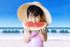 Child bites a watermelon at coast Royalty Free Stock Photography
