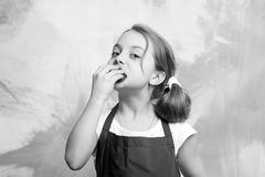 Child biting cake. Girl eating cupcake. Healthy food and diet concept. Baking and delicious bakery. Baby cook in red chef apron on colorful abstract wall royalty free stock photo