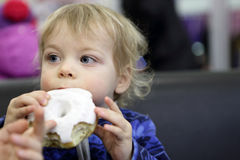 Child biting donut. At table in cafe stock image