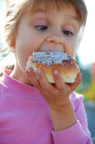 Child biting a doughnut. Funny cute little girl biting a doughnut royalty free stock image