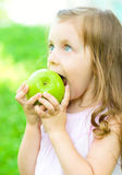 Child is biting green apple Royalty Free Stock Photo