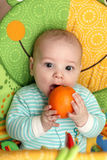 Child biting orange Royalty Free Stock Images