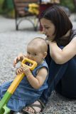 Child biting from a plastic shovel Royalty Free Stock Photos