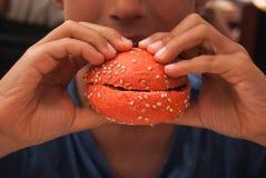 Child biting a red hamburger royalty free stock photos