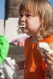 Child biting white ice cream Stock Photos