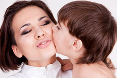Child bitting his mother cheek Stock Images