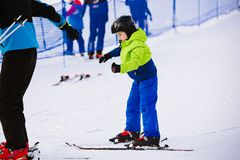 Child in a black helmet learns to ski with instructor Royalty Free Stock Images