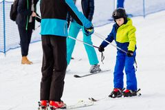 Child in a black helmet learns to ski with instructor Stock Photos