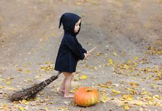 Child in black sorcerer or witch suit riding a broom near fresh. Pumpkin in fall foliage royalty free stock images