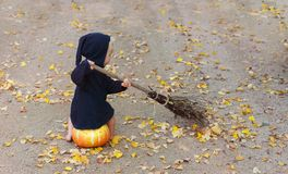 Child in black sorcerer or witch suit sits on pumpkin and sweep. Fall foliage by broom royalty free stock image