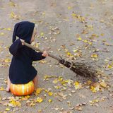 Child in black sorcerer or witch suit sits on pumpkin and sweep fall foliage, square frame. Child in black sorcerer or witch suit sits on pumpkin and sweep fall stock photography