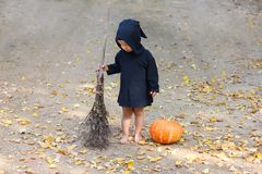 Child in black sorcerer or witch suit stands with broom near fre. Sh pumpkin in fall foliage stock image