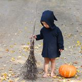 Child in black sorcerer or witch suit stands with broom near fresh pumpkin, square frame. Child in black sorcerer or witch suit stands with broom near fresh stock image