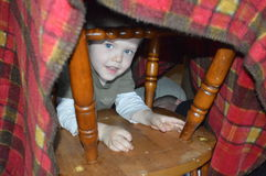 Child in blanket fort. A child peeks through the chair legs that hold up his blanket fort hideaway Royalty Free Stock Images