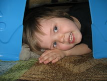 Child in blanket fort. A child peeks through the legs of a plastic table that hold up his blanket fort hideaway royalty free stock images