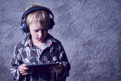 Child blond Boy listening to music or watching movie with headphones and using digital table Stock Photography