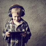 Child blond Boy listening to music or watching movie with headphones and using digital table Royalty Free Stock Image