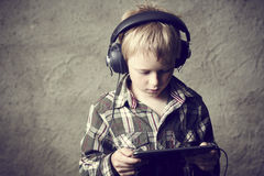 Child blond Boy listening to music or watching movie with headphones and using digital table Stock Images