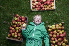 Child blond boy lying on the green grass with apples background, holding, eating and biting apple Stock Photos