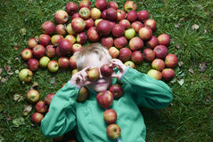 Child blond boy lying on the green grass background with apples glasses Stock Images