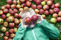 Child blond boy lying on the green grass background with apples glasses Royalty Free Stock Photo