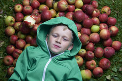 Child blond boy lying - resting on the green grass background with pile of apples Stock Photo