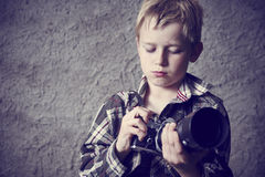 Child blond boy with Vintage photo film camera. Photographing outside. Concrete wall background stock images