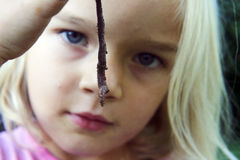 Child blond girl holding earthworm. Outside in the garden, portrait, summer, hand, backyard, nature Royalty Free Stock Photography