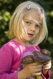 Child blond girl holding fresh mushrooms outside in the forest Royalty Free Stock Photo