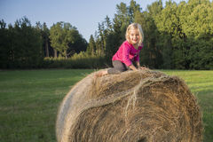 Child blond Girl by straw hay bale in field Stock Photo