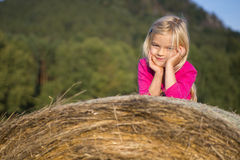 Child blond Girl by straw hay bale in field. Meadow, smiling, playing, portrait, summer, nature Stock Photography
