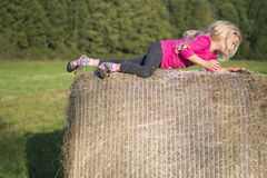 Child blond Girl by straw hay bale in field Royalty Free Stock Photos