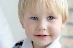 Child with blond hair and blue eyes. Portrait of child with blond hair and blue eyes Stock Image