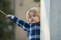 Child with blond hair in blue plaid shirt with stick royalty free stock images