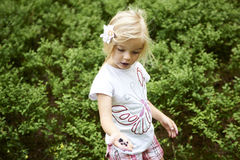 Child blond little girl picking fresh berries on blueberry field in forest. Child pick blue berry in the woods. Little girl playing outdoors. Summer family fun Stock Image