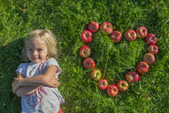 Child blond young Girl with red apples heart shape lying on the grass stock images