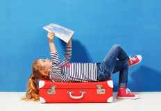 Child blonde girl with pink vintage suitcase and city map ready for summer vacation. Travel and adventure concept Stock Photos