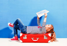 Child blonde girl with pink vintage suitcase and city map ready. For summer vacation. Travel and adventure concept Stock Photos