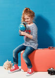 Child blonde girl with pink vintage suitcase study the globe. Travel and adventure concept Royalty Free Stock Image