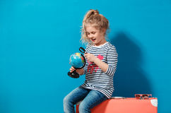 Child blonde girl with pink vintage suitcase study the globe. Travel and adventure concept Stock Photography