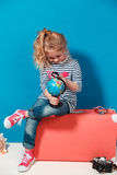 Child blonde girl with pink vintage suitcase study the globe. Travel and adventure concept Stock Photos