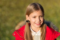 Child blonde long hair walking fall park background. Feel happy sunny autumn day. Girl happy wear coat with hood enjoy. Fall nature. Child wear coat for fall stock images