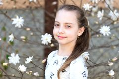 Child with blossoming flowers outdoor. Little girl on floral blossom in spring. Beauty kid with fresh look and long hair. Spring,. Easter and holidays stock photos