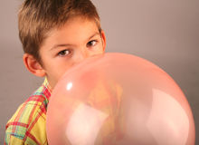 Child blowing balloon. Child blowing red balloon royalty free stock photo
