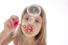 Child blowing bubbles Stock Photo