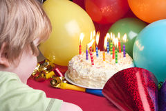 Child blowing candles out Stock Photo